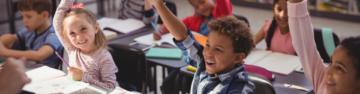 kids raising their hands in a classroom