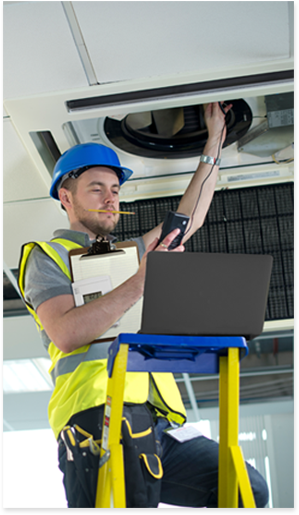 Technician on a ladder holding clipboard, data logger, meter, and laptop